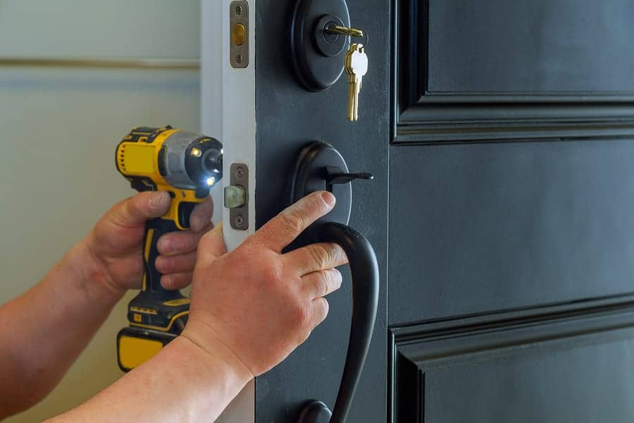 Closeup of a professional locksmith installing a new lock on a house exterior door with the inside internal parts of the lock