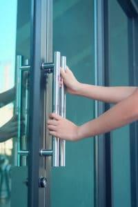 hand hold a door handle to open office.